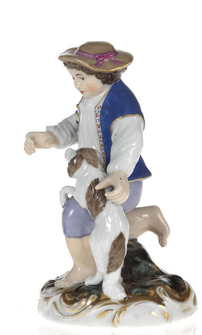 A Porcelain Figurine of a Boy with a Playful Puppy